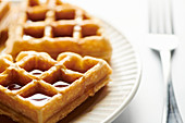 Belgian waffle pieces with syrup drpping down side