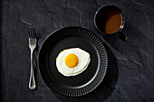 Sunnyside egg with fork and coffee on black surface with black plate and black coffee cup