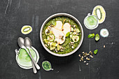 A green bowl with apple, pear, cucumber and kiwi
