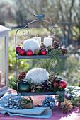 Weihnachtliche Dekoration auf Metall-Etagere mit Kerzen, Kugeln, Zapfen, Woll-Bällen und Koniferen-Zweigen