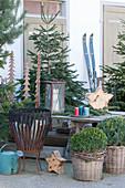 Ländliche Weihnachtsterrasse mit Nordmanntannen, Buchs, Feuerkorb, Holzsternen, Laterne und Sitzplatz