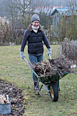 Frau mit Schubkarre voller Gartenabfall