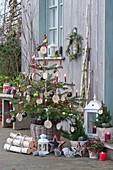 Nordmanntanne geschmückt mit Holzscheiben, Christbaumkugeln, Lichterkette und Kerzen, Sterne, Laternen und Birkenstämme als Deko