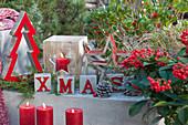 Moderne Weihnachtsdekoration auf der Terrasse mit Buchstaben, Sternen, Tannenbäumchen, Windlicht und Kerzen