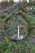 Kranz aus Hemlocktanne mit Kerze, Stern und Zapfen als Weihnachtsdeko an Lärche gehängt