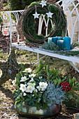 Weihnachtliches Arrangement mit bepflanzter Kupferschale, Kranz, Kerzen und Stern an Gartenbank