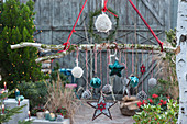 Weihnachts-Mobile als hängende Deko mit Sternen, Zapfen, Kugeln und Woll-Bommeln an Birkenast