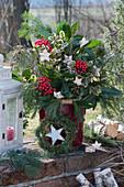 Weihnachtsstrauß mit Kiefer, Tanne, Kirschlorbeer, Skimmie und Stechpalme im Eimer auf der Gartenmauer