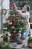 Frau schmückt Nordmanntanne mit roten Holzsternen und Zapfen als Weihnachtsbaum