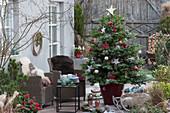 Weihnachtsterrasse mit geschmückter Nordmanntanne als Weihnachtsbaum, Korbsessel mit Fell als Sitzplatz