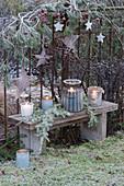 Weihnachtliches Arrangement mit Lichtern und Rauhreif am Gartenzaun, Holzsterne an Kiefernzweig