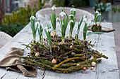 Schneeglöckchen in Kranz aus flechtenbewachsenen Zweigen, Birke, Weide und Gräsern, dekoriert mit Zwiebeln