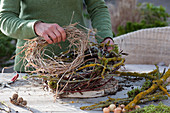 Schneeglöckchen in Kranz aus Zweigen : Frau windet Kranz aus flechtenbewachsenen Zweigen, Birke, Weide und Gräsern