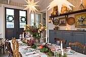 Festlich gedeckter Tisch im weihnachtlich dekorierten Esszimmer
