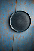 An empty blue plate on a blue wooden surface