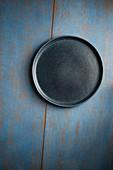 Leerer blauer Teller auf blauem Holzuntergrund