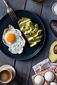 A fried egg and a wholemeal bread with avocado for breakfast