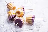 Frozen soya yoghurt on sticks with blueberries, vanilla and mango