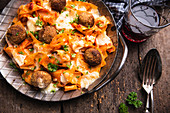 Gratinated tagliatelle with chickpea balls, tomato sauce and almond cheese