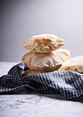 Pita bread stacked on a tea towel against a grey background