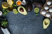 Zutaten für ein Low-Carb-Frühstück: Eier, Avocado und Kräuter