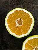 A halved ugli fruit on a dark surface
