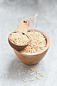 Rice in a wooden bowl and a wooden scoop