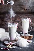 Heiße weiße Schokolade mit Zuckerstangen und Marshmallows