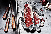 Rindersteaks in Alufolie, daneben alte Messer