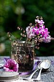 Sträußchen aus Lichtnelke, Wegerichblüten und Plattährengras in alter Teedose, Petunien-Blüte, Löffel