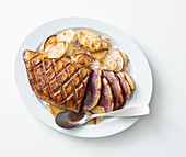 Duck breast a honey glaze on a potato and apple gratin