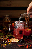 Pouring tonic water into an apple and blackberry gin and tonic