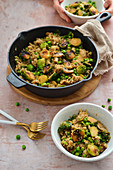 Quinoa with caramelized Brussels sprouts green peas and sweet potatoes dish in a pan A healthy vegetarian dish