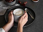 Hände halten Tasse mit Dattel-Soja-Drink
