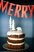 Layer cake decorated with wintry fondant icing below festive banner