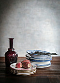 Red glass carafe and stacked vintage plated on wooden table
