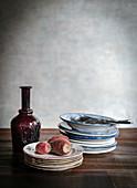 Rote Glaskaraffe und gestapelte Vintage-Teller auf Holztisch