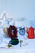 Wreath of chillies, retro alarm clock and vintage enamel coffee pot on festively set table