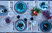 Blue-and-white speckled crockery and fairy lights on festively set table