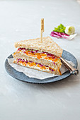 A wholemeal sandwich with cream cheese, radicchio, carrots and celmentines
