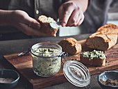 Homemade herb butter being spread onto bread