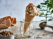 Macadamia nut ice and salted caramel sauce in a cone