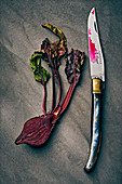 A halved beetroot with a knife