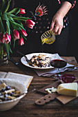 Woman drizzling olive oil over pasta with radicchio, panceta and Parmesan