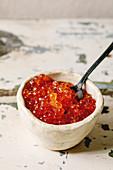 Roter Lachskaviar mit Löffel in Keramikschälchen