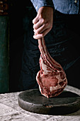 Man s hands holding raw uncooked black angus beef tomahawk steak on bones on linen table cloth. Rustic style