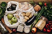 Zero waste food shopping. Fruit and vegetables in cotton bags, pasta, cereals and legumes in glass jars, herbs and spices on wooden background. Healthy food, clean eating, eco friendly, no plastic concept. Flat lay, top view