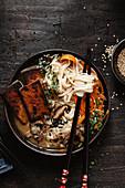 Vegane asiatische Suppe mit Nudeln, Pilzen, Karotten und Tofu