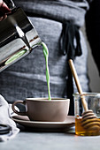 Matcha latte being poured into a cup