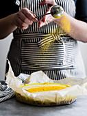 Vegan golden milk cheesecake being prepared by a chef in a kitchen